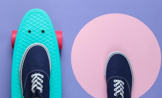 Cruiser board en sneakers op paarse achtergrond met een roze pastel cirkel. hipster jeugdconcept. zomerplezier. bovenaanzicht