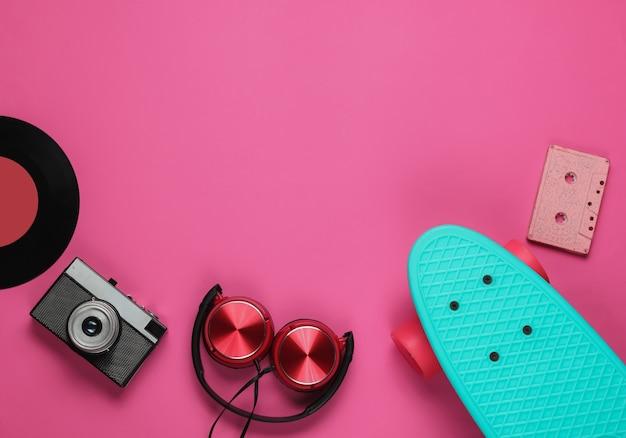 Cruiser board hoofdtelefoon film camera audio cassette vinyl record op roze achtergrond