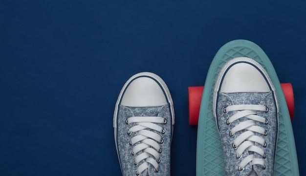 Cruiser board met sneakers op een klassiek blauw. jeugdvermaak