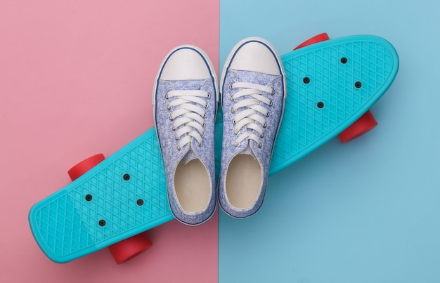 Cruiser board met sneakers op roze blauw pastel. jeugd entertainment. hipster-outfit