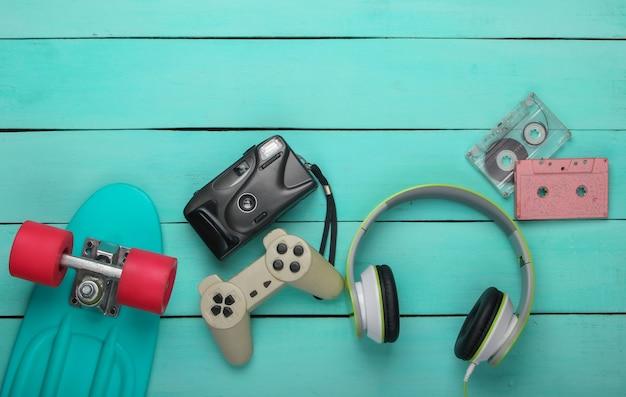 Cruiserboard, audiocassette, koptelefoon, gamepad, camera op blauwe houten ondergrond