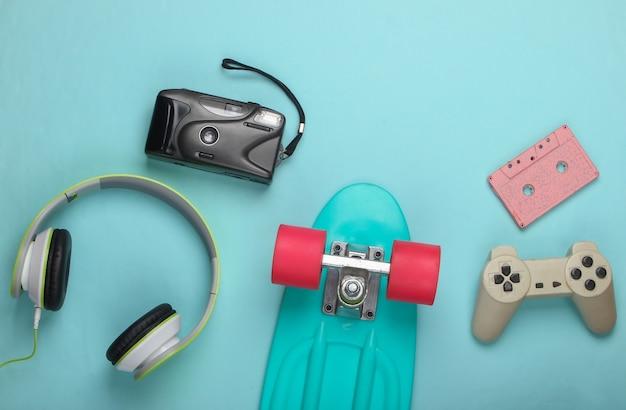 Cruiserboard, gamepad, stereohoofdtelefoon, audiocassette, filmcamera op een blauw oppervlak