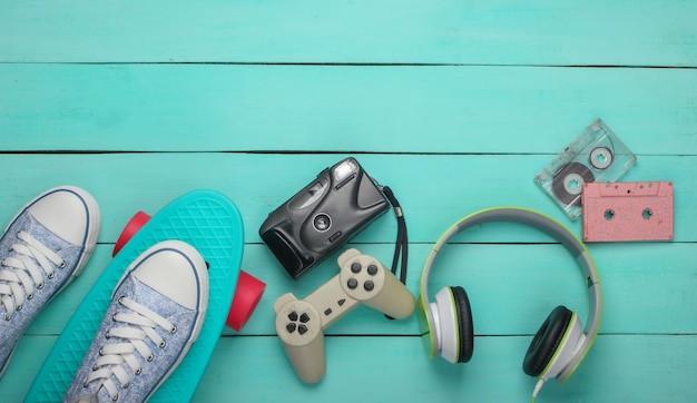Cruiserboard, sbeakers, audiocassette, koptelefoon, gamepad, camera op blauw houten oppervlak