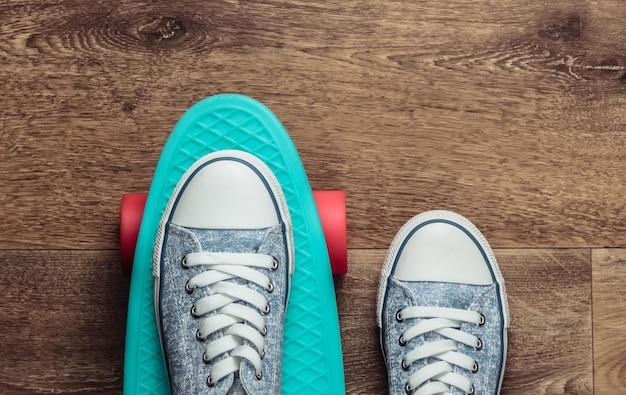 Cruiserbord met sneakers op de vloer. bovenaanzicht