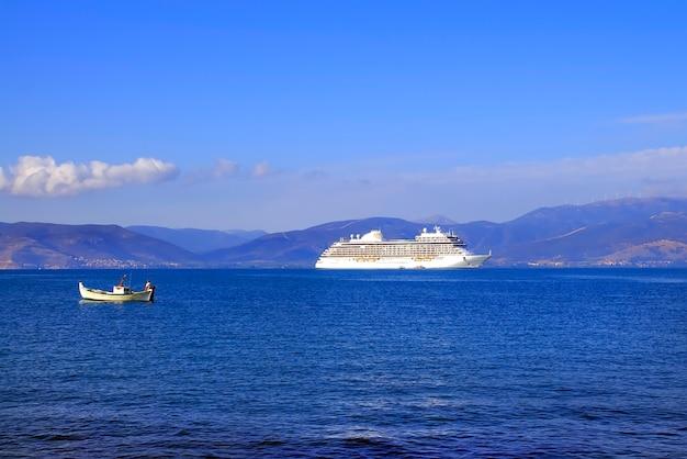 Cruiseschip en vissersboot in n argolische golf, nafplio.