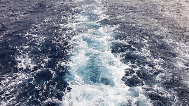 Cruiseschip of parcours op het oppervlak van de blauwe rode zee. zeewaterschipsleep met witte schuimende golf. bovenaanzicht van de diepe oceaan. perspectief van een golf van wit water.