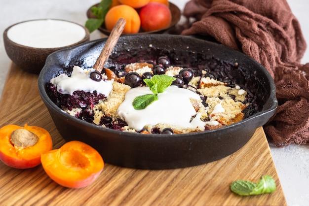 Crumble in gietijzeren pan met zwarte bessen en abrikoos, natuurlijke yoghurt en munt.