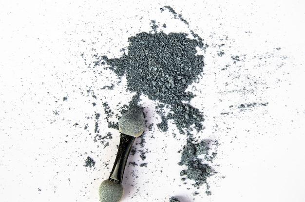 Crumbs van verpletterde grijze glanzende oogschaduw die op witte achtergrond wordt geïsoleerd