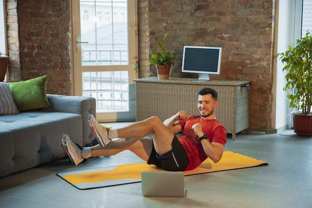 Crunches. jonge blanke man traint thuis tijdens de quarantaine van de uitbraak van het coronavirus, doet fitnessoefeningen, aerobics. video opnemen of online streamen. wellness, sport, bewegingsconcept.