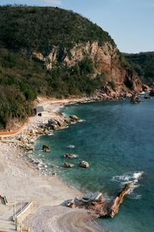 Crvena glavica strand tegen de achtergrond van de zee en de bergen in de budva riviera