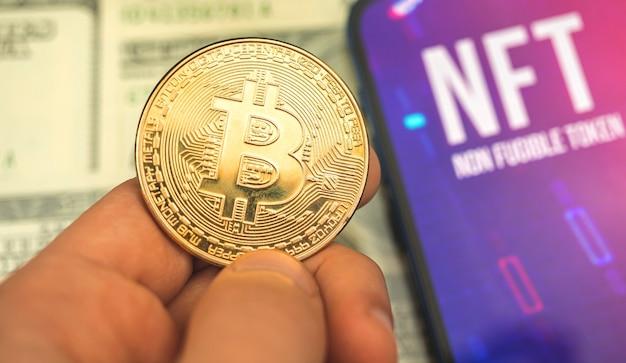 Crypto-gegevenseenheid, gouden bitcoin in de hand en nft-logo op het scherm, zakelijke en financiële crypto-concept en achtergrondfoto