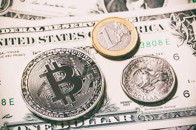 Cryptocurrency bitcoin-muntstuk dichtbij één dollarmuntstuk en één euro muntstuk op dollarbankbiljet.