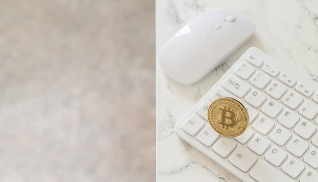 Cryptocurrency gouden bitcoin op wit computertoetsenbord naast muis op marmeren tafel