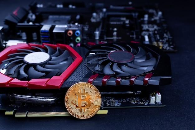 Cryptocurrency mining concept met gouden bitcoin munten naast een computer performante videokaart zwarte achtergrond