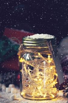 Crystal pot met lampen met een gift ernaast, terwijl het sneeuwt