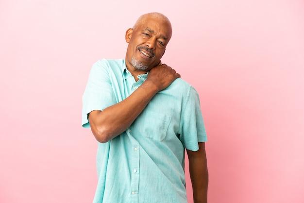 Cubaanse senior geïsoleerd op roze achtergrond die lijdt aan pijn in de schouder omdat hij moeite heeft gedaan