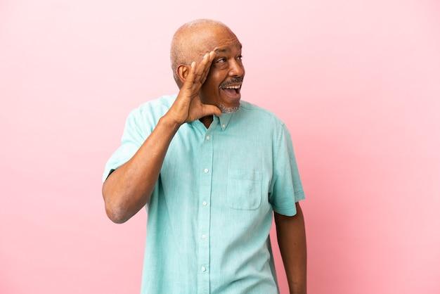 Cubaanse senior geïsoleerd op roze achtergrond schreeuwen met mond wijd open naar de zijkant