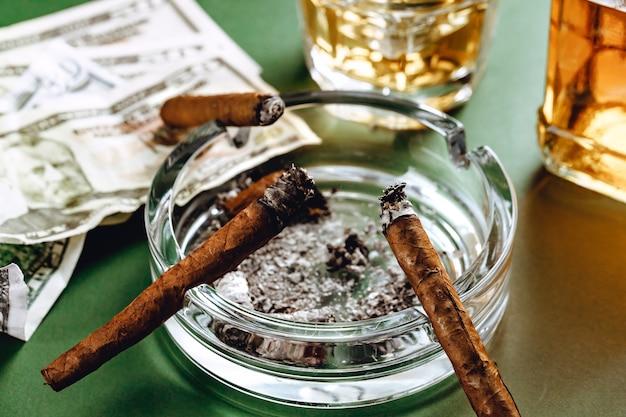 Cubaanse sigaar en geld op groene ondergrond