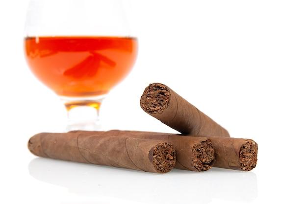 Cubaanse sigaren en glas met rum geïsoleerd op een witte achtergrond
