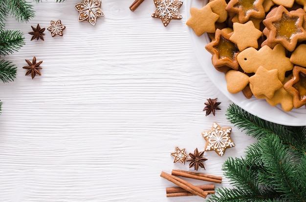 Culinaire achtergrond met vers gebakken kerstmispeperkoek, kruiden en dennentakken. kopieer ruimte