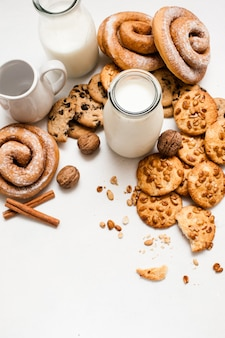 Culinaire achtergrond van zelfgebakken winkel, bovenaanzicht vrije ruimte. volkoren scones, gebakken broodjes, walnoten en kruiden tot in de buurt van flessen melk op witte tafel. concept van heerlijke ontbijtkoekjes