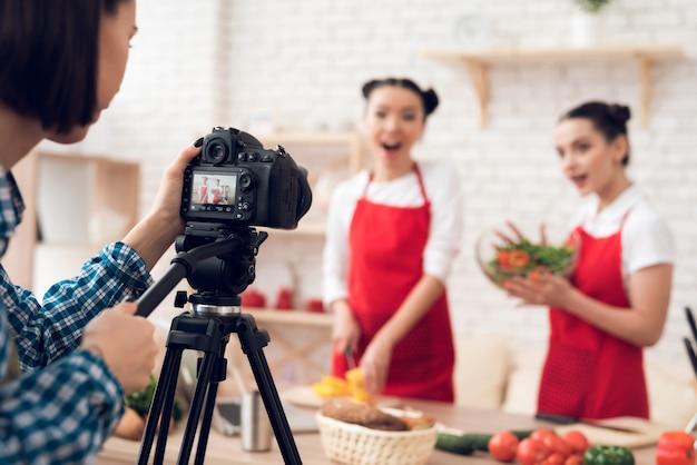 Culinaire bloggers die blokjes paprika's mengen met een salade.