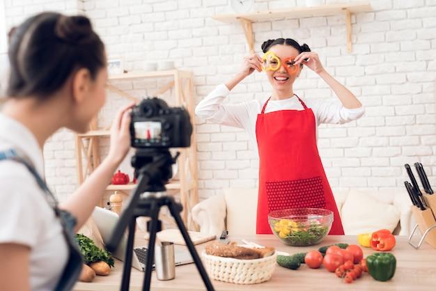 Culinaire bloggers die in blokjes gesneden paprika met salade mengen.