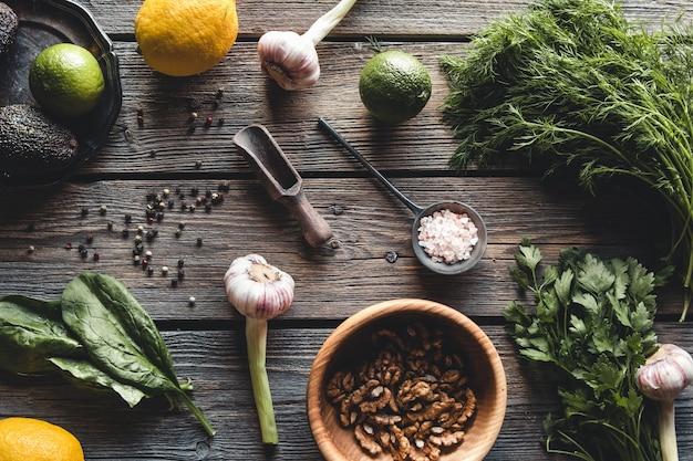 Culinaire groene kruiden, spinazie, dille, peterselie, avocado in een houten doos die op wit wordt geïsoleerd