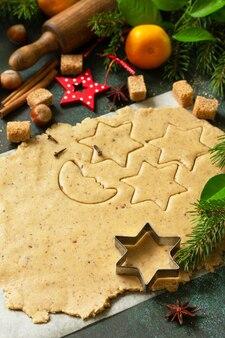 Culinaire kerst achtergrond. deeg en ingrediënten voor het bakken van peperkoek.