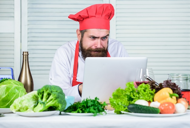 Culinaire keuken. vitamine. gelukkig bebaarde man. chef-kok recept. gezond eten koken. rijpe hipster met baard. vegetarische salade met verse groenten. dieet biologisch voedsel. zeker in zijn keuze.