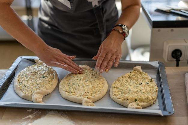 Culinaire masterclass. close-up van mensenhanden die khachapuri voorbereiden. traditioneel georgisch kaasbrood. georgisch eten. grote onherkenbare familie kokende handen dicht omhoog