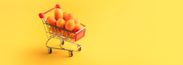 Cumquat of kumquat in een winkelwagentje op gele achtergrond, fruit shopping concept