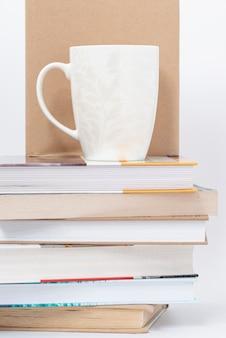 Cup geplaatst op stapel boeken