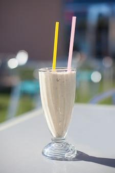 Cup met een smoothie met twee rietjes