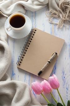 Cup met koffie, kladblok, tulpen, pen op witte houten tafel. concept van de lente