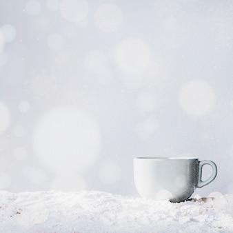 Cup op bank van sneeuw en sneeuwvlokken