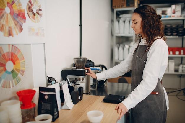 Cup taster girl tasting degustation coffee quality test. jonge vrouwenbarista met koffiemolenmolen.