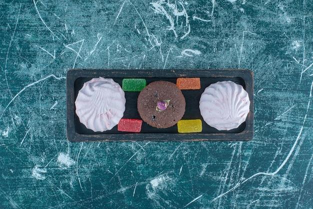 Cupcake, koekjes en marmelades in een klein dienblad op blauwe achtergrond. hoge kwaliteit foto