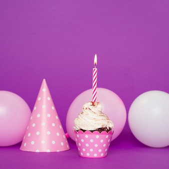 Cupcake met aangestoken kaars naast hoed