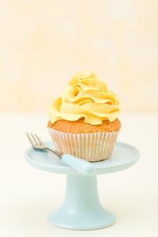 Cupcake met gele roomdecoratie op blauwe tribune - pastelkleurbanner
