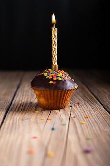 Cupcake met glazuur en aangestoken kaars