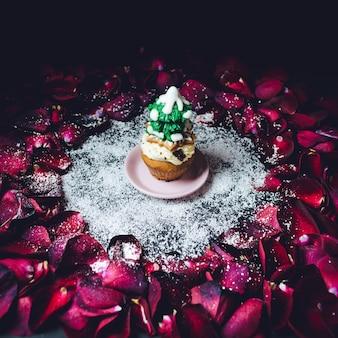 Cupcake met glazuur firboom op bovenstaande tribunes in de cirkel van rozenblaadjes