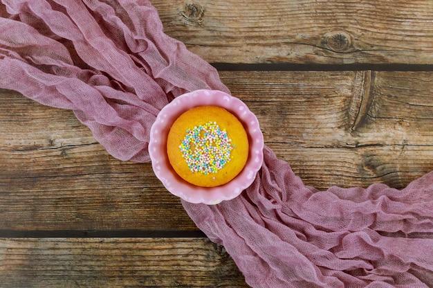 Cupcake met hagelslag in roze kom op houten tafel.