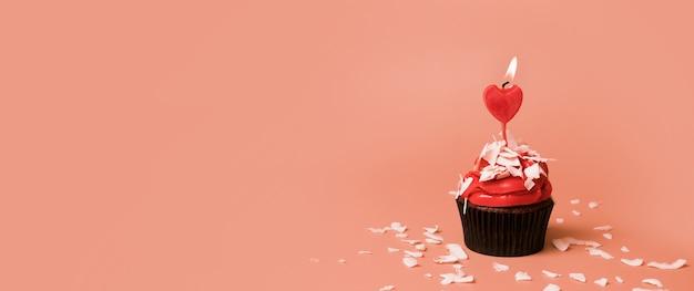 Cupcake met kaars hartvorm en decor voor valentijnsdag banner met kopie ruimte