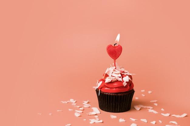Cupcake met kaars in de vorm van een hart - snoep voor valentijnsdag met kopie ruimte