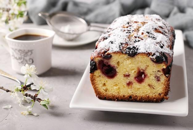 Cupcake met kersen op een witte plaat op lichtgrijze achtergrond en een kopje koffie. detailopname