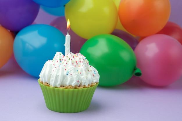 Cupcake met kleurrijke verjaardagskaars en ballons