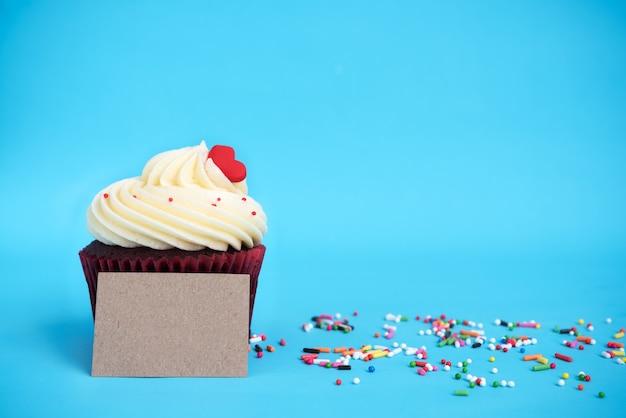 Cupcake met rood hart, kleurrijke sprinkles en bruine noot