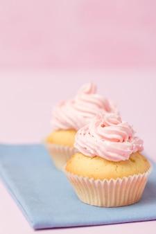 Cupcake met roze buttercream op pastelkleur roze achtergrond die wordt verfraaid. zoete mooie cake