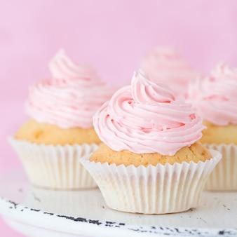 Cupcake met roze buttercream op pastelkleur roze achtergrond die wordt verfraaid.